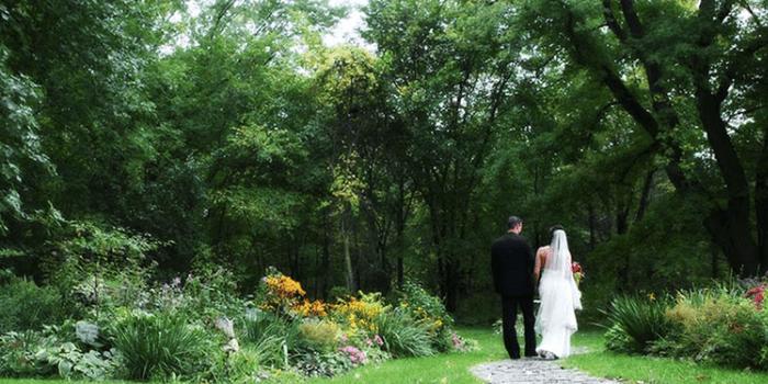 Bride and Groom walking down cobblestone trail near woods.